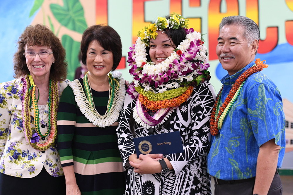 Sara King receives congratulations from Dr. Jane Foley (far left), senior vice president of the Milken Educator Awards; Hawaii First Lady Dawn Amano-Ige; and Hawaii Governor David Y. Ige.
